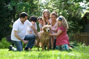 A family of five with their dog looking at the dog. They are going to a family therapist in Houston TX