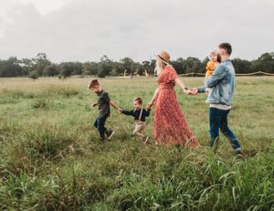 A family of five running in the field feeling relieved from grief symtoms because they are getting grief counseling in Houston and The woodalnds tx